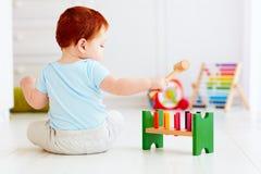 Nettes Säuglingsbaby, das mit hölzernem Hammerblockspielzeug spielt Stockbild