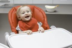 Nettes Säuglingsmädchen, das im Babystuhl sitzt und Kamera betrachtet Stockfotos