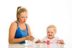 Nettes Säuglingsmädchen, das learining ist, um zu essen Stockbild