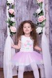 Nettes süßes kleines Mädchen, das auf einer Wiege mit Blumen schwingt lizenzfreies stockfoto