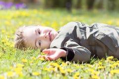 Nettes süßes kleines Mädchen, das im Frühjahr Gras mit Gänseblümchen legt stockfotografie
