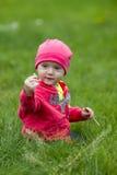 Nettes Schätzchen, das auf Gras sitzt Stockbilder