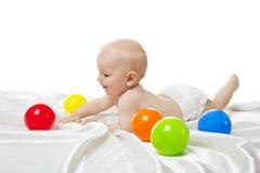 Nettes Schätzchenspiel im Bett mit Farbenkugeln Stockbilder