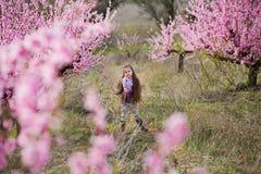 Nettes schönes stilvolles gekleidetes blondes Mädchen, das auf einem Feld des jungen Pfirsichbaums des Frühlinges mit rosa Blumen Lizenzfreies Stockfoto