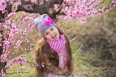 Nettes schönes stilvolles gekleidetes blondes Mädchen, das auf einem Feld des jungen Pfirsichbaums des Frühlinges mit rosa Blumen Stockfoto