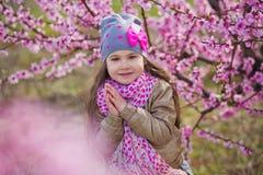Nettes schönes stilvolles gekleidetes blondes Mädchen, das auf einem Feld des jungen Pfirsichbaums des Frühlinges mit rosa Blumen Stockbilder