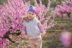 Nettes schönes stilvolles gekleidetes blondes Mädchen, das auf einem Feld des jungen Pfirsichbaums des Frühlinges mit rosa Blumen Lizenzfreie Stockfotografie