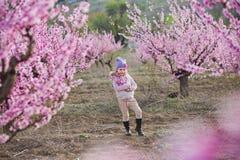 Nettes schönes stilvolles gekleidetes blondes Mädchen, das auf einem Feld des jungen Pfirsichbaums des Frühlinges mit rosa Blumen Stockfotos