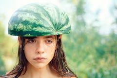 Nettes sch?nes M?dchen, das eine Wassermelone auf ihrem Kopf tr?gt Sonniger Tag E stockfotos