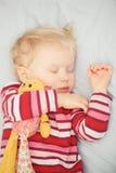 Nettes schlafendes blondes Baby mit Spielzeug Stockbilder