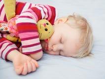 Nettes schlafendes blondes Baby mit Spielzeug Lizenzfreie Stockfotografie