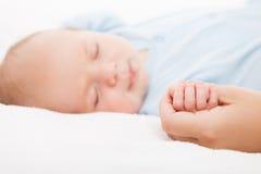 Nettes schlafendes neugeborenes Babykind, das Mutterhand hält Stockfoto