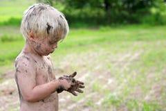 Nettes schmutziges Kind, das draußen im Land spielt Lizenzfreie Stockfotografie
