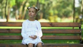 Nettes Schulmädchen, das allein auf Bank im Park, herum schauend, Mangel an Freunden sitzt stock video