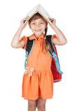 Nettes Schulmädchen mit Buch auf seinem Haupt und einem roten Rucksack auf ihr Stockfoto