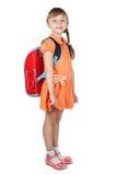 Nettes Schulmädchen mit einem roten Rucksack auf ihren Schultern Lizenzfreies Stockbild