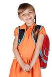 Nettes Schulmädchen mit einem roten Rucksack auf ihren Schultern Stockfotografie
