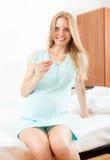 Nettes schwangeres blondes Sitzen auf Bett mit Thermometer zu Hause Lizenzfreie Stockfotografie