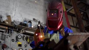 Nettes Schweißermädchen in der Uniform in der Garage, die mit Schweißensausrüstung arbeitet Frauen ` s Arbeit in der Kunst stock video