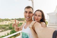 Nettes selfie eines jungen Paares, das an der Kamera, ein Symbol des Friedens umarmt und lächelt lizenzfreie stockfotografie
