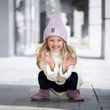 Nettes Sitzen und Lachen des kleinen Mädchens in der Strickmütze stockfotografie