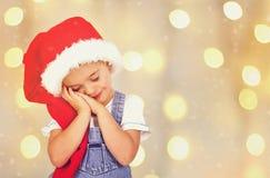 Nettes sleppy Weihnachtsbaby in rotem Sankt-Hut Stockfotografie