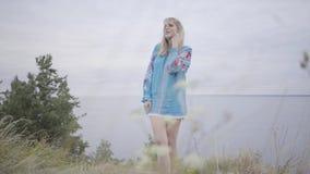 Nettes sorgloses kaukasisches Mädchen, welches das lange Sommermodekleid betrachtet überzeugt der Kamera genießt Stände auf trägt stock video