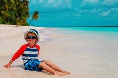 Nettes Spiel des kleinen Jungen mit Wasser und Sand auf Strand lizenzfreie stockbilder