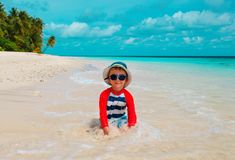 Nettes Spiel des kleinen Jungen mit Wasser und Sand auf Strand lizenzfreie stockfotografie