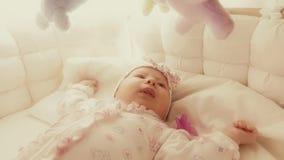 Nettes spielerisches Baby in ihrem Feldbett stock footage