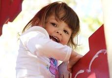 Nettes spielerisches kleines Mädchen, das oben steigt Stockbild