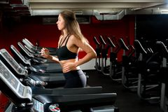 Nettes sportliches Mädchen, das auf einer Tretmühle an der Turnhalle läuft stockbilder
