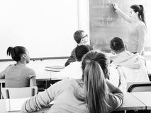 Nettes Studentenmädchen löst Aufgabe nahe Tafel in Klassenzimmer mathe stockfotografie