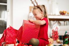 Nettes super aufgeregtes junges Mädchen, das großes rotes Weihnachtsgeschenk beim Sitzen auf Wohnzimmerboden öffnet Offene Famili stockfoto