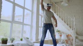 Nettes Tanzen des jungen Mannes beim Erfahrung unter Verwendung 360 VR-Kopfhörergläser virtueller Realität auf Bett zu Hause erha stock video footage