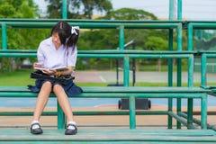 Nettes thailändisches Schulmädchen ist, lesend sitzend und auf einem Stand Lizenzfreies Stockfoto
