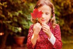 Nettes träumerisches Kindermädchen, das hinter rotem Herbstblatt im Garten sich versteckt Stockbild