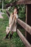 Nettes träumerisches Kindermädchen, das am rustikalen Bretterzaun mit Teddybären aufwirft stockbild