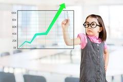 Nettes tragendes Geschäftskleid des kleinen Mädchens und Schreiben über Leistungsdiagramm Bürohintergrund lizenzfreies stockfoto