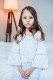 Nettes tragendes Nachthemd des kleinen Mädchens, das auf dem Bett sitzt Lizenzfreie Stockfotos
