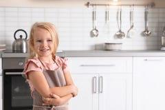 Nettes tragendes Schutzblech des kleinen Mädchens nahe Ofen in der Küche stockfotografie