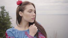 Nettes unabhängiges Mädchen, welches das lange Sommermodekleid betrachtet überzeugt der Kamera genießt Stände auf dem Hintergrund stock footage