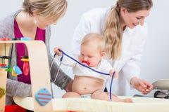 Nettes und gesundes Baby, das mit dem Stethoskop während der Routineüberprüfung spielt stockfoto
