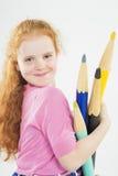 Nettes und glückliches rothaariges Caucasain-Mädchen, das mit enormem Penci spielt Lizenzfreie Stockfotografie