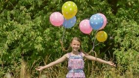 Nettes und hübsches Mädchen mit bunten Bällen befestigte zu ihrem Haar und zu Zöpfen auf ihrem Kopf Lustige Idee mit Ballonen Lizenzfreies Stockbild