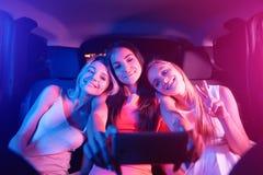 Nettes und nettes Mädchen sitzen im Auto zusammen Blonde Mädchen stehen auf ihren Freund ` s Schultern still Brunette ist Stockfotografie