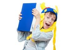 Nettes verärgertes stilvolles Kind, das den lustigen Hut hält ein sehr großes blaues Buch trägt Stockfotografie