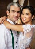Nettes verheiratetes Paar, das nahe der Backsteinmauer steht Stockbilder