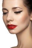 Nettes vorbildliches Gesicht mit hellem klassischem Abendmake-up, Eyeliner auf Augen, roter Lippenstift stockfotos
