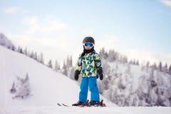Nettes Vorschulkind, Junge, glücklich fahrend im österreichischen Skiort Ski Lizenzfreies Stockfoto